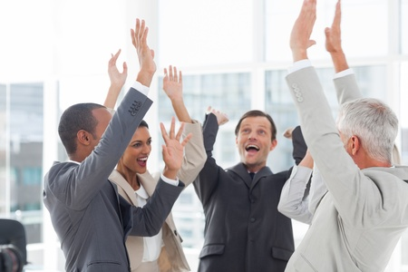 Grupo de gente sonriente de negocios levantando sus manos en el lugar de trabajo