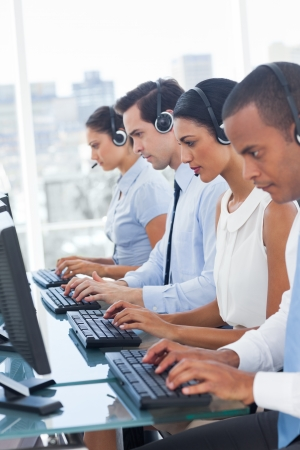 operators: Call center employees sitting in line in a workplace Stock Photo