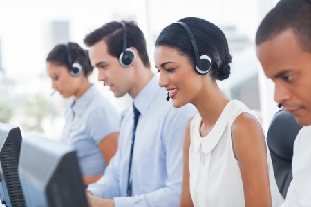 Smiling call center employees sitting in line with their headset photo
