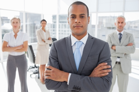 Serious businessman standing with arms crossed in front of colleagues photo