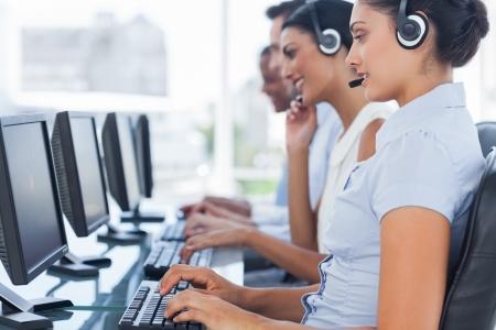 コール センターの労働者がコンピューター上の人々 を支援しながら行に座っています。