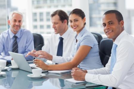 gente sentada: Sonriendo gente de negocios lluvia de ideas en la sala de reuniones