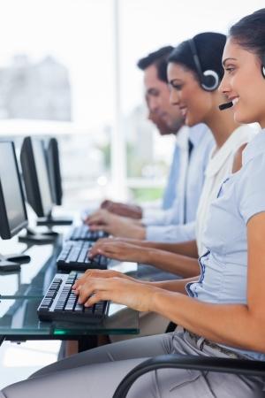 servicio al cliente: Personas alegres de los empleados del centro de llamadas de trabajo en equipos Foto de archivo