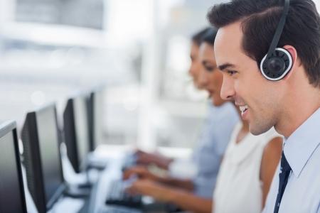 笑みを浮かべてコール センター エージェント コンピューター上で作業に焦点を当てる 写真素材