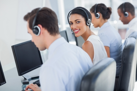 Smiling call centre employee looking over shoulder while having a discussion photo