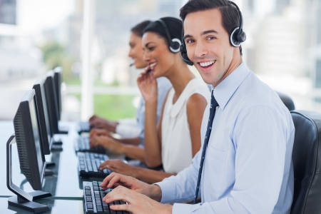 Joyful agent working in a call centre with his headset photo