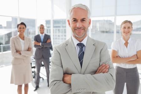 彼の後ろに同僚の前で立っているを折られた腕を持ったビジネスマン