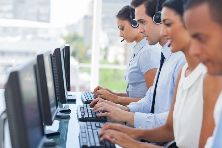 customer support team: Call centre employees working on computers with their headset