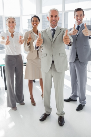 Group of business people giving thumbs up in the meeting room photo