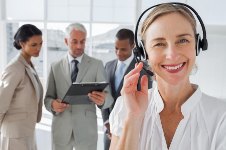Close up of smiling woman standing with a headset with colleagues working behind photo