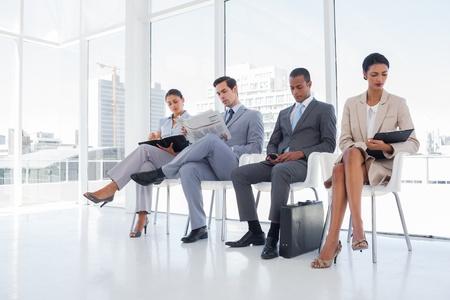 Gut gekleidete Business-Leute sa�en zusammen in einem Wartezimmer
