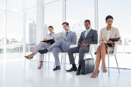 reading newspaper: Well dressed business people sat together in a waiting room Stock Photo