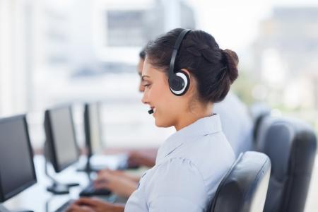 servicio al cliente: Atractiva morena de trabajo en un centro de llamadas con sus auriculares Foto de archivo