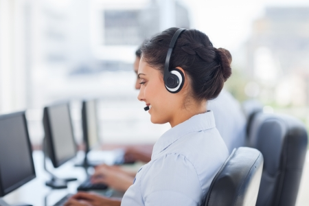 Attractive brunette working in a call centre with her headset Stock Photo - 20467983