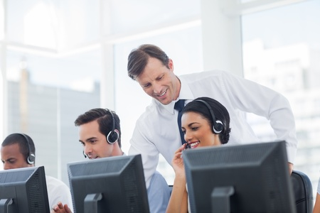 Manager listening to call centre employee working on computer Stock Photo