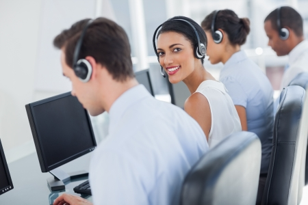 Attractive call centre employee looking over shoulder while wearing a headset photo