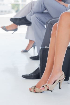 business woman legs: Legs of business people in line in a waiting room Stock Photo