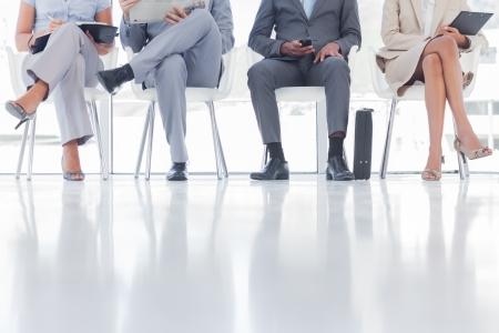 file d attente: Un groupe de gens d'affaires en attente dans une salle d'attente Banque d'images