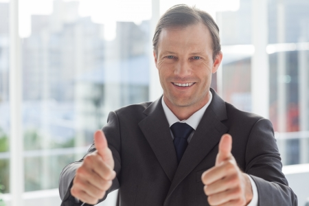 Smiling businessman giving thumbs up in an office photo