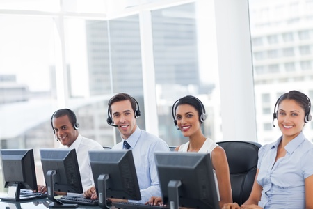 Line of call centre employees smiling and working on computers photo