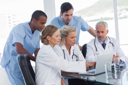 personal medico: Equipo médico serio que usa una computadora portátil en una oficina brillante Foto de archivo