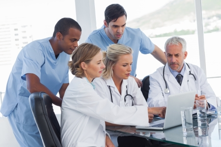 healthcare: Serious medical team using a laptop in a bright office