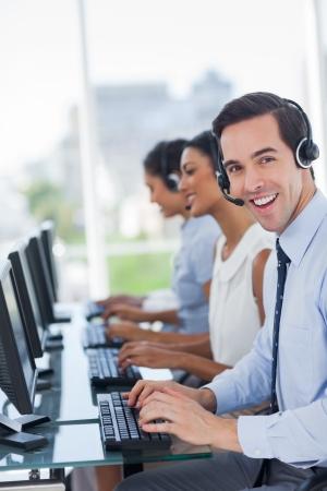 call center agent: Joyful chiamata agente centro di lavoro con il suo auricolare Archivio Fotografico