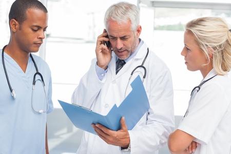 personal medico: Tres médicos preocupados llamar a alguien