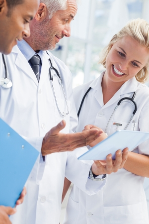 Doctor explaining something in his tablet to his medical team Stock Photo - 20501320