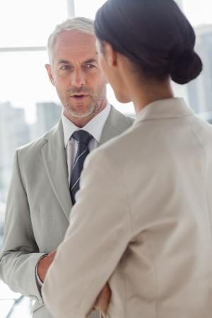 dialogo: Hombre de negocios concentrado escuchando compa�era de trabajo en la oficina