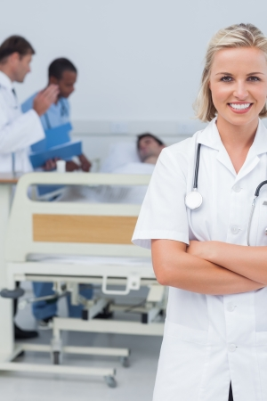 Smiling blonde nurse crossing her arms and looking at the camera in front oh her team and a patient photo