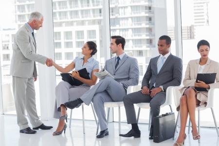 file d attente: Directeur d'affaires accueillant assis dans une salle d'attente