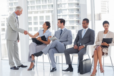 man waiting: Director welcoming businesswoman sat in a waiting room