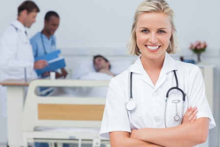 Blonde nurse crossing her arms and looking at the camera in front oh her team and a patient photo