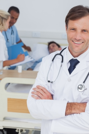 Smiling doctor looking at the camera in front of his team and a paitent photo