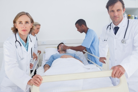 Serious doctors ready to move with patient during emergency photo