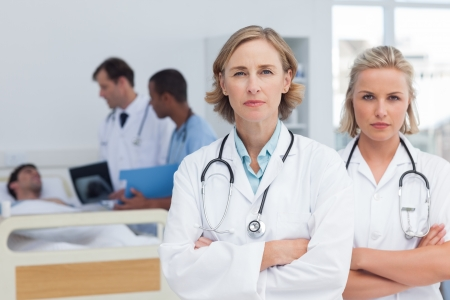 Two serious women doctors standing in front of medical team and a patient photo