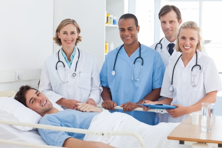 Medical team and patient smiling and looking at the camera photo