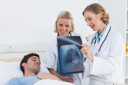Two women doctors showing x-ray to a patient in hospital photo