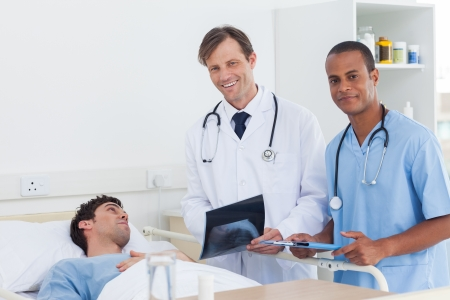 Doctors with radiography standing next to a patient and looking at the camera photo
