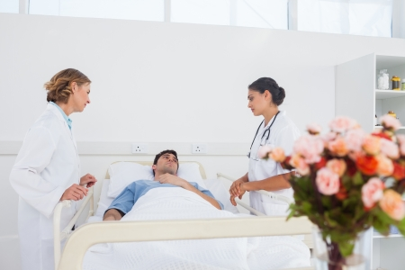 Lying patient in his bed looking to his two women doctors photo