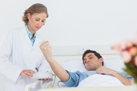 Woman doctor taking the blood pressure of male patient in a hospital photo
