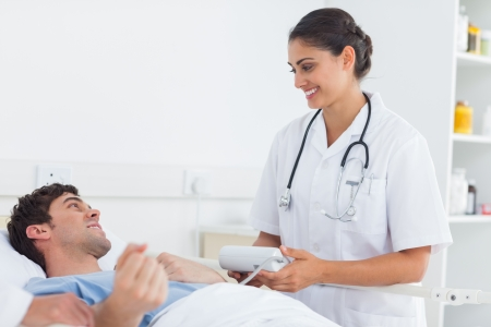 Attractive doctor taking the blood pressure of a patient in a hospital photo