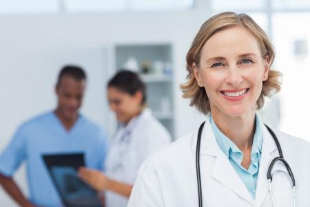 lekarz: Kobieta lekarz uśmiecha się i patrząc do kamery, podczas gdy zespół medyczny pracuje