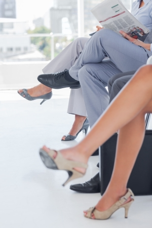 Legs of business people in a waiting room photo
