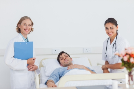 Smiling doctors and lying patient looking at the camera photo