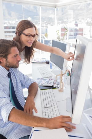 editors: Editors reviewing photographs on computer at their desk in bright office Stock Photo