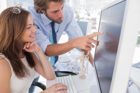 monitor de computadora: Hombre que se�ala algo a su pareja en la pantalla en la oficina creativa