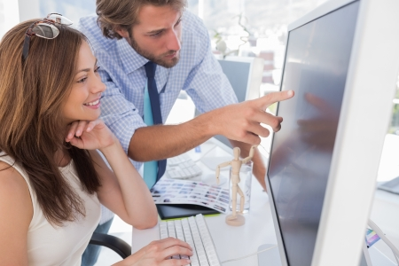 pc monitor: Man pointing something to his partner on screen in creative office