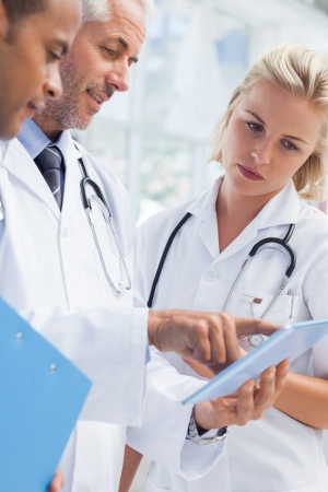 tablet pc: Doctor showing something in his tablet to his medical team